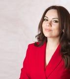一件红色古典夹克的一名年轻微笑的妇女 免版税图库摄影