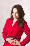 一件红色古典夹克的一名年轻微笑的妇女 免版税库存照片