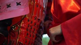 一件红色和服的一个女孩在装甲的一名武士后站立并且将从刀鞘得到tanto匕首 影视素材