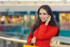 一件红色外套的商城女孩谈话在智能手机 免版税库存照片
