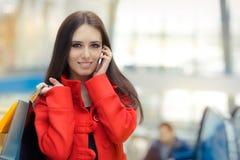 一件红色外套的商城女孩谈话在智能手机 图库摄影