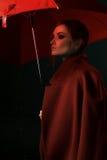一件红色外套的女孩有一把红色伞的在雨中 免版税库存照片