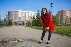 一件红色外套的美丽的女孩在公园胡同 库存图片