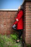 一件红色外套的美丽的妇女在一个砖墙上在城市 库存照片