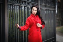 一件红色外套的美丽的妇女 免版税库存图片