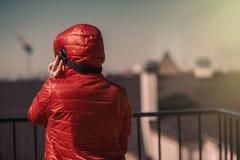 一件红色夹克和耳机的美丽的女孩 阳台的一个女孩听到音乐的和唱歌 图库摄影