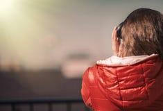 一件红色夹克和耳机的美丽的女孩 阳台的一个女孩听到音乐的和唱歌 库存照片