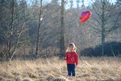 一件红色夹克的女孩有心形的气球的 免版税库存照片