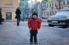 一件红色夹克的小男孩哭泣在街道的 库存照片