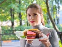 一件红色女衬衫的女孩吃一个饼 库存图片