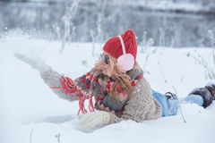 一件红色帽子和毛线衣的美丽的女孩在桃红色的雪与耳机和围巾 图库摄影