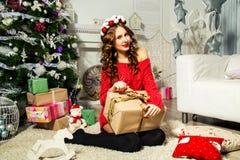 一件红色毛线衣开头礼物的女孩在圣诞树附近 Chri 免版税库存图片