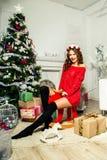 一件红色毛线衣的女孩坐玩具麋在圣诞树附近 免版税库存图片