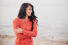一件红色毛线衣的少妇走在海滩的 库存图片