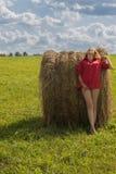 一件红色短的衬衣的美丽的女孩有开放脚的在绿草的一个草甸和有反对蓝天的一个干草堆的与云彩 图库摄影