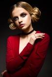 一件红色礼服有深刻的领口的和黑圆环的美丽的女孩在他的手指 与明亮的构成的模型 库存图片
