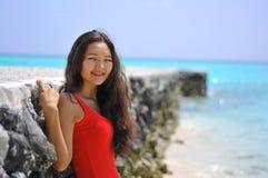 一件红色礼服的亚裔女孩在热带海滩的码头附近 库存照片