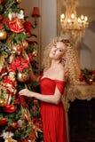 一件红色礼服的卷曲白肤金发的女孩微笑在圣诞树附近的 免版税库存照片