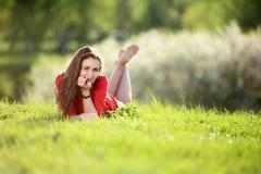 一件红色礼服的女孩在一个晴天在草甸 免版税库存照片