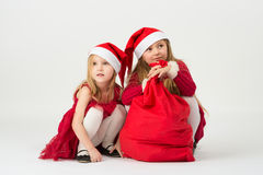一件红色礼服的女孩在响铃圣诞老人开会 免版税库存照片