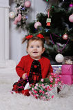 一件红色礼服的小女孩在圣诞树的背景 免版税库存照片