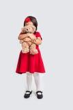 一件红色礼服的小女孩有玩具熊的 库存图片