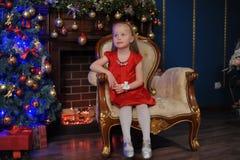 一件红色礼服的小白肤金发的孩子 免版税图库摄影