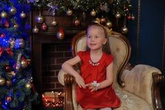 一件红色礼服的小白肤金发的孩子 免版税库存照片