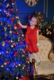 一件红色礼服的小白肤金发的孩子 免版税库存图片