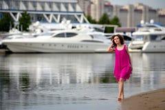 一件红色礼服的少妇和在水的卷发沿岸航行 免版税库存图片