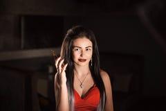 一件红色礼服的引人入胜的浅黑肤色的男人在她的手上的拿着一个电话 免版税库存照片