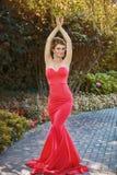 一件红色礼服的美丽的女孩在公园 图库摄影