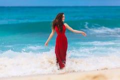 一件红色礼服的美丽的妇女在热带沿海 免版税库存图片