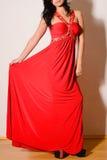 一件红色礼服的美丽的浅黑肤色的男人有珠宝的 免版税库存照片