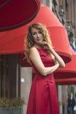 一件红色礼服的美丽的端庄的妇女 库存照片