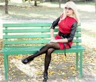 一件红色礼服的聪慧的金发碧眼的女人在长凳 免版税库存照片