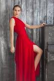 一件红色礼服的豪华妇女在长沙发 免版税库存图片