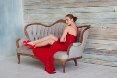 一件红色礼服的豪华妇女在长沙发 库存图片