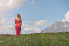 一件红色礼服的赤裸女性在日落的一个领域 免版税库存图片