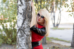 一件红色礼服的金发碧眼的女人在秋天的一棵树 免版税库存图片