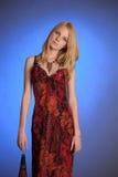 一件红色礼服的金发碧眼的女人在蓝色背景 免版税图库摄影