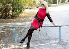 一件红色礼服的金发碧眼的女人坐保护在公园 免版税库存图片