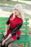 一件红色礼服的金发碧眼的女人坐长凳 库存图片