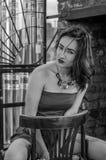 一件红色礼服的年轻美丽的女孩坐在一个咖啡馆的一把木椅子在一条街道上在市利沃夫州 图库摄影