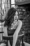 一件红色礼服的年轻美丽的女孩坐在一个咖啡馆的一把木椅子在一条街道上在市利沃夫州 库存照片