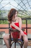 一件红色礼服的年轻美丽的女孩坐在一个咖啡馆的一把木椅子在一条街道上在市利沃夫州 免版税库存图片