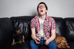 一件红色衬衣和蓝色牛仔裤的一个年轻人在家坐并且与他们的狗一起打电子游戏 可怜的人哭泣和angr 免版税库存图片