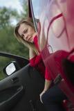 一件红色衬衣和驾驶的一辆红色汽车女孩 免版税库存照片