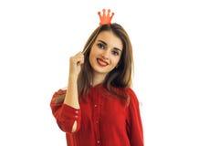 一件红色衬衣的一个美丽的少妇微笑对与纸冠的照相机的在头 免版税库存图片