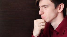 一件红色衬衣的一个年轻人在他的右臂倾斜他的下巴 股票视频